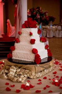 White 4 tier wedding cake with red roses going up corner of each tier