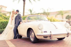Newlyweds standing in front of car at Rosen Shingle Creek