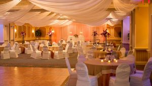 Wedding Reception Tables with White Chairs and Beige Table Cloth