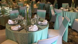 Wedding Reception Tables with White Chairs and Turquoise Table Cloth