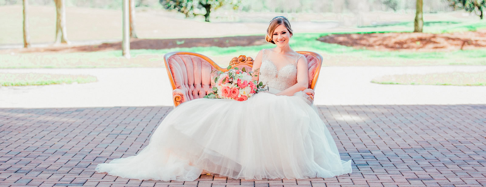 Bride sitting outside on couch holding flowerrs