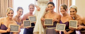 """Bridesmains hold chalkboard signs with the words """"Wait Until You See Her"""" in front of bride"""