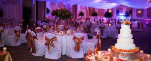 White chairs with orange bows, white table cloths, 4 tier cake with orange flowers