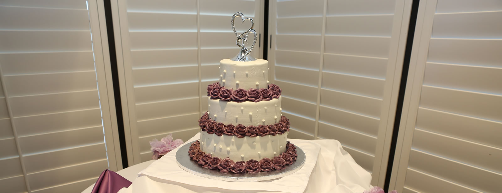 White 3 tier cake with purple roses and silver hearts on top