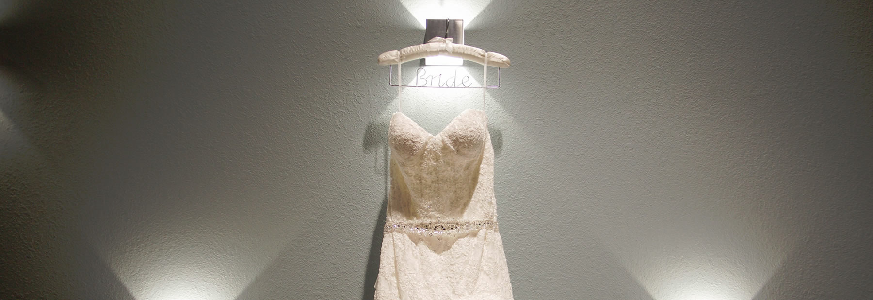 Wedding dress hanging on wall surrounded by lights