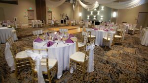 Weddings table setup with white table cloths, purple napkinds, and gold and white chairs