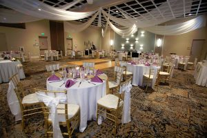 Clarion table set up for wedding reception with white and gold chairs, white tablecloth, and purple napkins