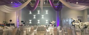 Clarion Wedding Reception with white tables and chairs, purple streamers from ceiling