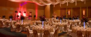 White table cloths, white chairs, flower center pieces in ballroom