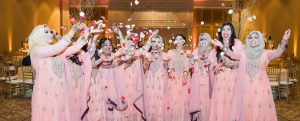Indian women weaing pink gowns throwing flower petals in air