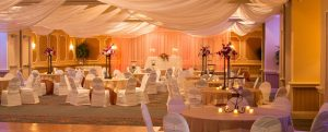 Wedding reception with orange ambient light, white chairs, at Rosen Plaza