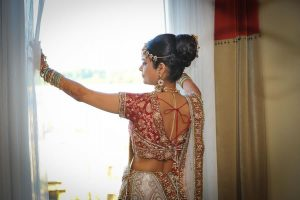 Indian bride standing in front of window looking out