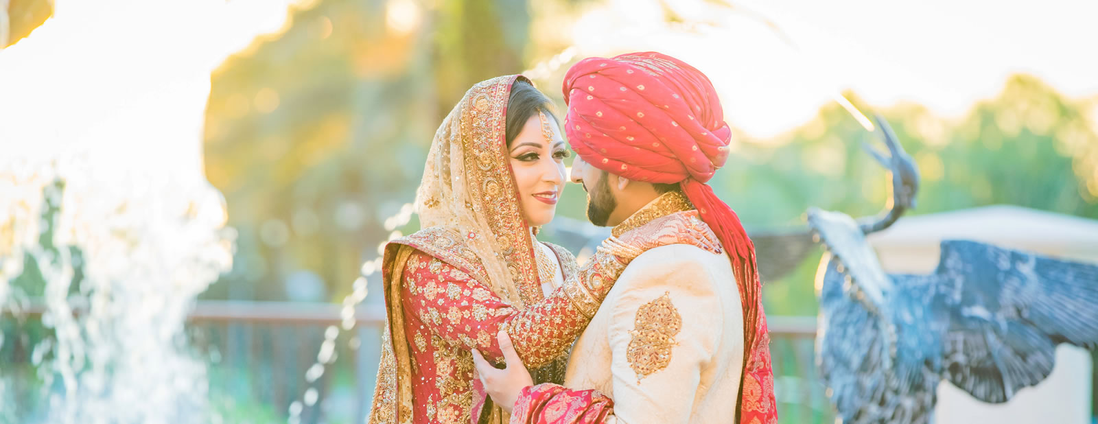Indian newly weds staring into each others eyes while standing in front of fountain